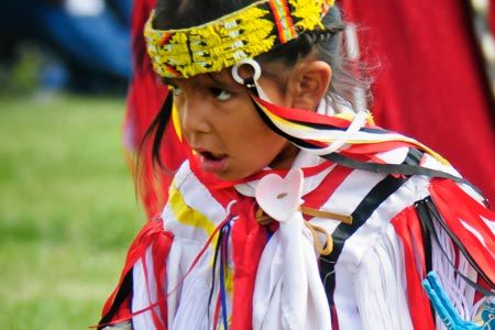 Child dancing in Native American regalia